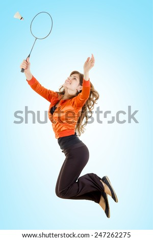 Girl playing badminton jumping in the air catching shuttlecock with racket , Full length of young woman playing badminton - stock photo