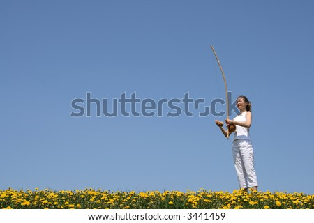 Girl playing berimbau (traditional Brazilian music instrument) in flowering spring meadow. - stock photo