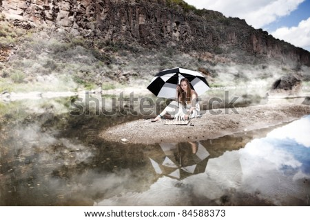 Girl playing chess alone under an umbrella by the river in morning fog and drizzle