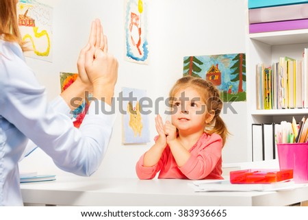 Girl playing finger games with teacher - stock photo