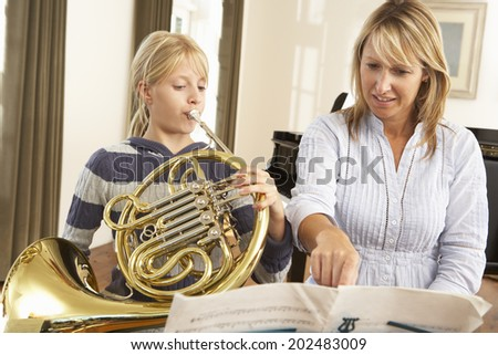 Girl playing French horn in music lesson - stock photo