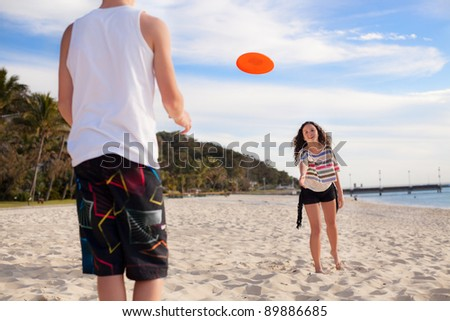 Girl playing frisbee on the beach - stock photo