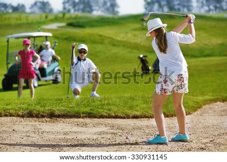 Girl playing golf and  and hitting from bunker