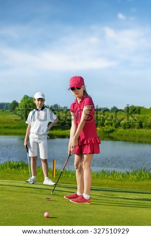 Girl playing golf and hitting by putter on green