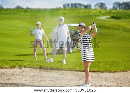 Girl playing golf and  hitting from bunker  - stock photo