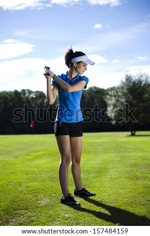 Girl playing golf on grass in summer - stock photo