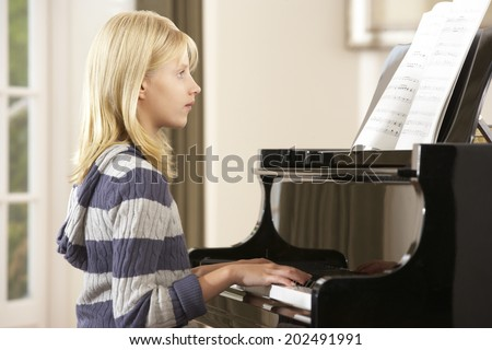 Girl playing grand piano at home - stock photo