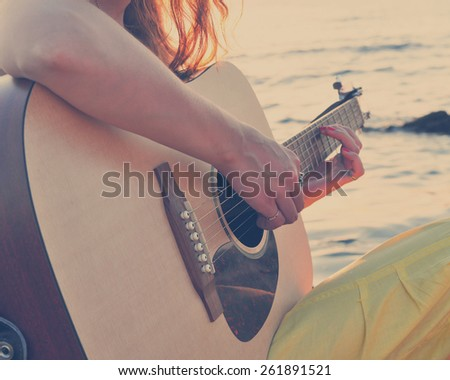 Girl playing guitar at the seacoast