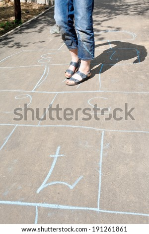 girl playing in hopscotch on urban alley in sunny day
