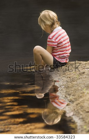 Girl playing in sand at water's edge - stock photo
