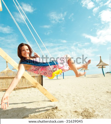 Girl playing on a swing-set on the beach - stock photo