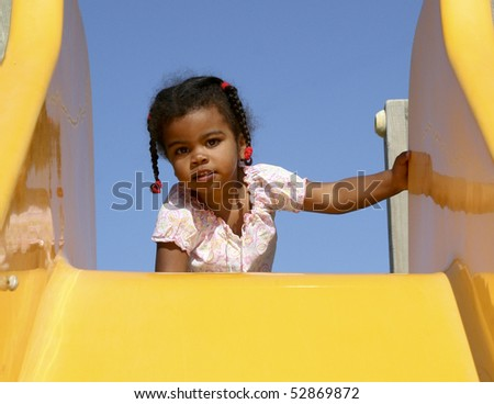 Girl playing on slide A beautiful african american child at the top of a playground slide.  - stock photo