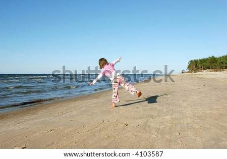 Girl playing on the beach - stock photo
