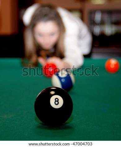 Girl playing pool in the nightclub interior.
