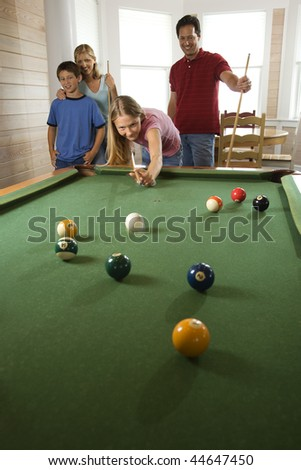 Girl playing pool with family in background. Vertically framed shot. - stock photo