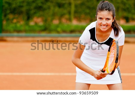 Girl playing tennis at a clay court holding the racket - stock photo