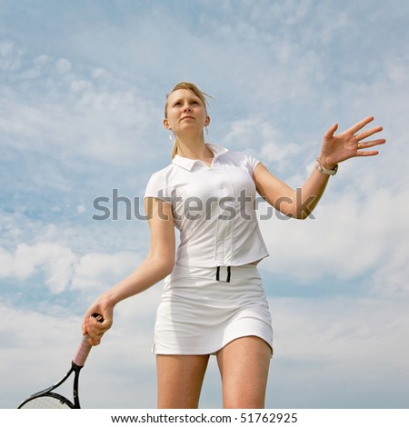 Girl playing tennis on background of sky - stock photo