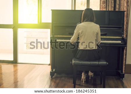 Girl playing the piano - stock photo