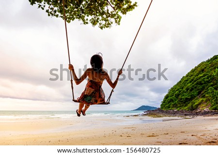 Girl playing the swing on beach - stock photo