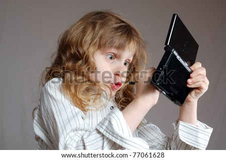girl playing video game on a mini computer - stock photo