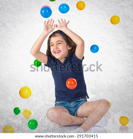 Girl playing while raining colored balls over grey background - stock photo