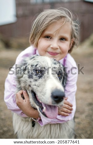 Girl playing with a Border Collie in nature - stock photo