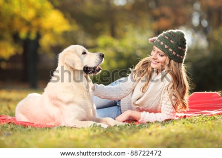 Girl playing with a labrador retriever dog in the park - stock photo