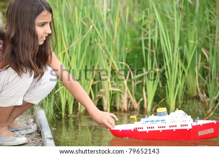 Girl playing with a toy boat on a lake - stock photo