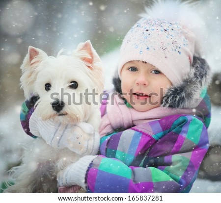 girl playing with a white dog winter snow happiness - stock photo