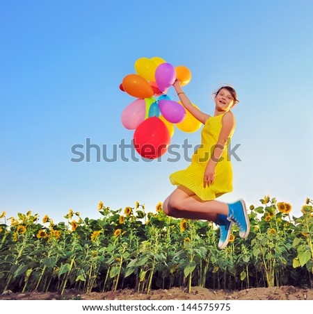 girl playing with balloons in summer time - stock photo