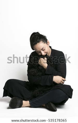 Girl playing with black puppy Scotch Terrier