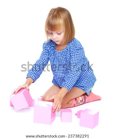Girl playing with blocks on a white background. - stock photo