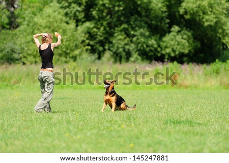 Girl playing with dog on green grass - stock photo