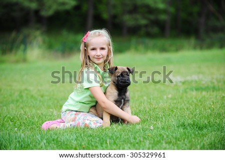 girl playing with dogs on grass - stock photo