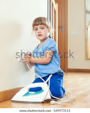 girl  playing with electric iron at home