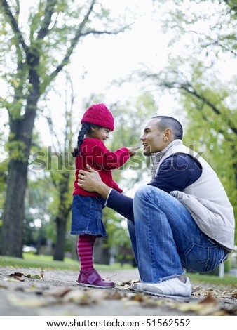 Girl (3-4) playing with father in park - stock photo