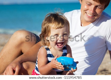 Girl playing with father on the beach - stock photo