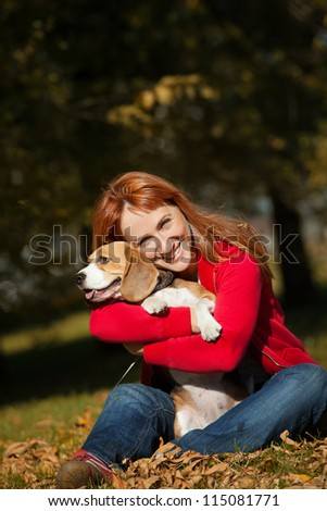 Girl playing with her beagle dog in autumn park - stock photo