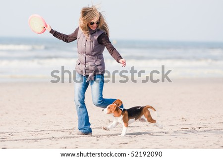 Girl playing with her beagle puppy  on beach