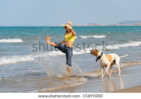 girl playing with her dog on the beach - stock photo
