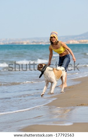 girl playing with her dog on the beach