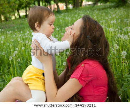 girl playing with her sister on the meadow - stock photo