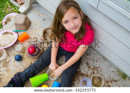 girl playing with mud in a messy soil smiling portrait looking from high point - stock photo