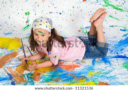 Girl playing with painting with the background painted - stock photo