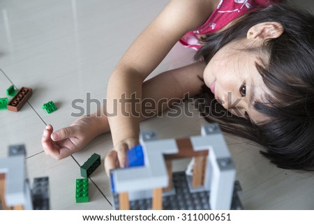 Girl playing with plastic blocks intentions . - stock photo