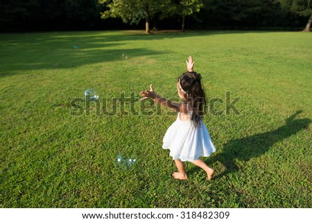 Girl playing with soap bubbles - stock photo
