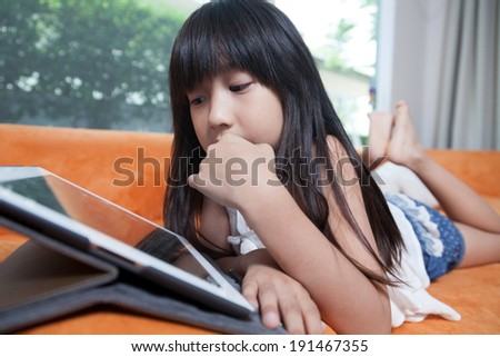 Girl playing with tablet. Lying on the orange sofa at home.
