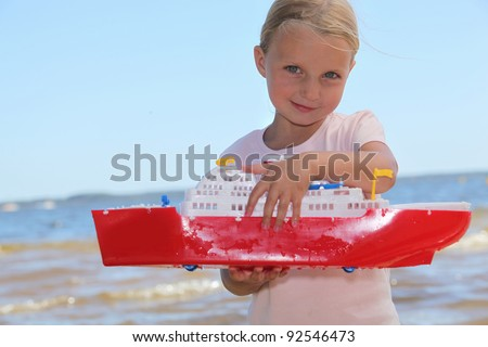 Girl playing with toy boat - stock photo