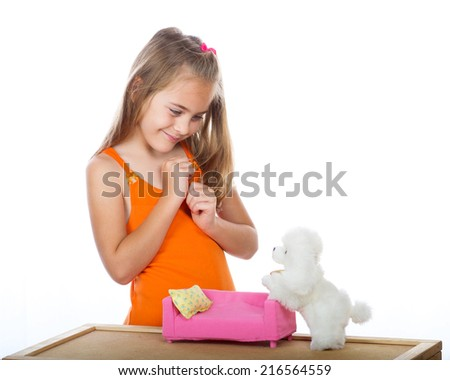 Girl playing with toys Seven year old girl plays with stuffed dog and sofa. - stock photo
