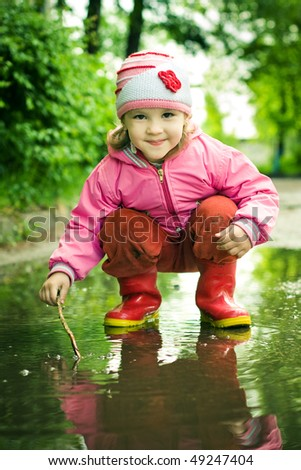 girl plays in the puddle - stock photo